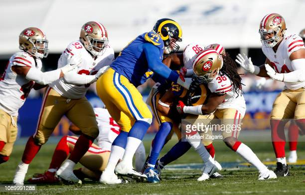 Marcell Harris and DJ Jones of the San Francisco 49ers tackle Robert Woods of the Los Angeles Rams during the game at the LA Memorial Coliseum on...