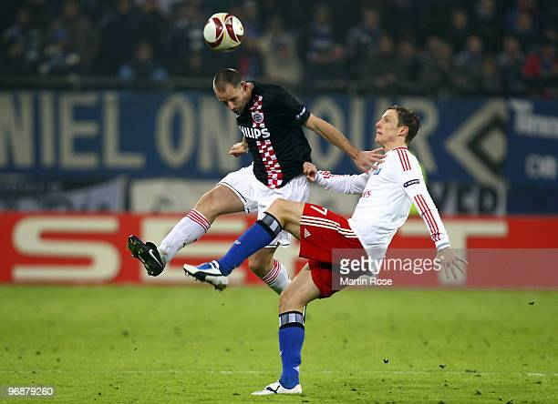 Marcell Jansen of Hamburg and Andre Ooijer of Eindhoven compete for the ball during the UEFA Europa League knockout round first leg match between...