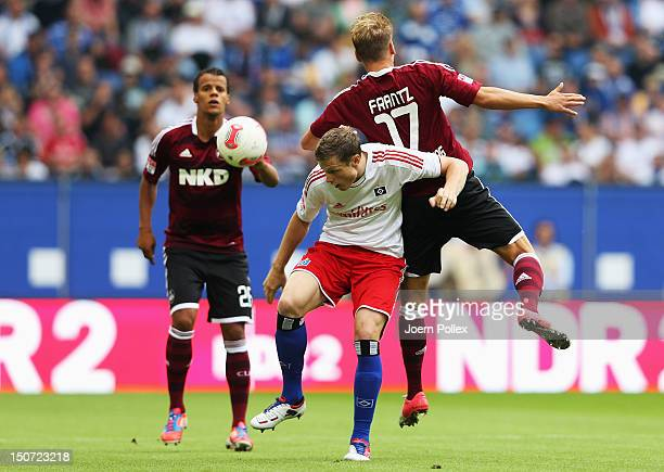 Marcell Jansen of Hamburg and Mike Frantz of Nuernberg compete for the ball during the Bundesliga match between Hamburger SV and 1 FC Nuernberg at...