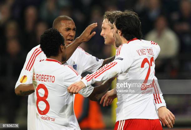 Marcell Jansen of Hamburg is celebrated by his team mates after scoring his team's second goal during the UEFA Europa League round of 16 second leg...