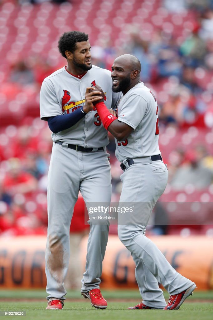 Marcell Ozuna #23 and Jose Martinez #38 of the St. Louis Cardinals react in the ninth inning of the game against the Cincinnati Reds at Great American Ball Park on April 14, 2018 in Cincinnati, Ohio. The Cardinals defeated the Reds 6-1.