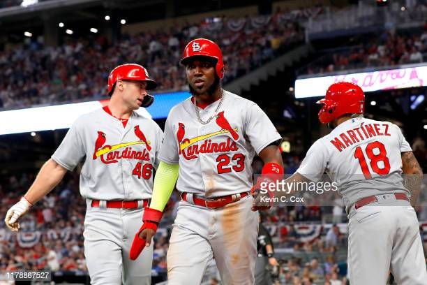 Marcell Ozuna and Paul Goldschmidt of the St Louis Cardinals are congratulated by their teammate Carlos Martinez after scoring runs on a double by...