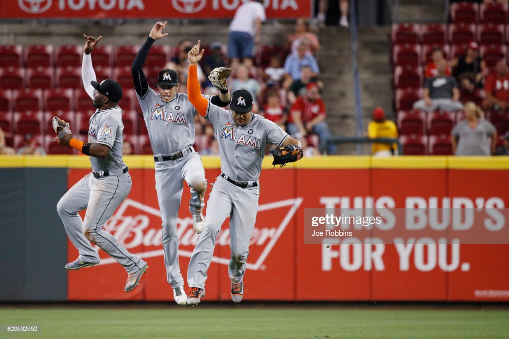 Marcell Ozuna #13, Christian Yelich #21 and Giancarlo Stanton #27 of the Miami Marlins celebrate after the final out of the game against the Cincinnati Reds at Great American Ball Park on July 21, 2017 in Cincinnati, Ohio. The Marlins defeated the Reds 3-1.