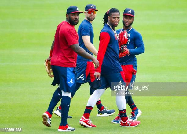 Marcell Ozuna, Ender Inciarte, Ronald Acuna Jr. #13 and Ozzie Albies of the Atlanta Braves head to the outfield during the summer workouts at Truist...