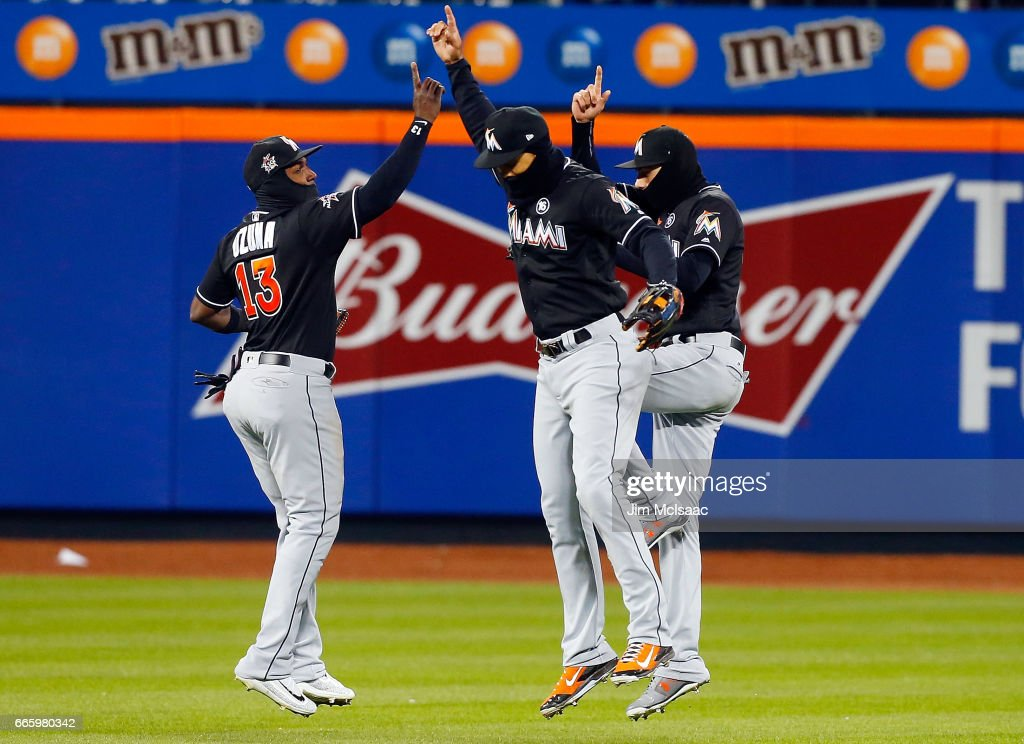 Marcell Ozuna #13, Giancarlo Stanton #27 (C) and Christian Yelich #21 of the Miami Marlins celebrate after defeating the New York Mets at Citi Field on April 7, 2017 in the Flushing neighborhood of the Queens borough of New York City.