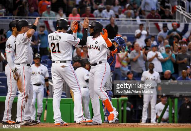 Marcell Ozuna of the Miami Marlins celebrates with Christian Yelich after hitting a home run during the game against the New York Mets at Marlins...