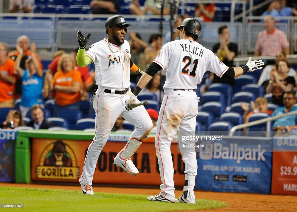 Marcell Ozuna #13 of the Miami Marlins celebrates with teammate Christian Yelich #21 after hitting a seventh inning solo home run against the Atlanta Braves at Marlins Park on October 1, 2017 in Miami, Florida.