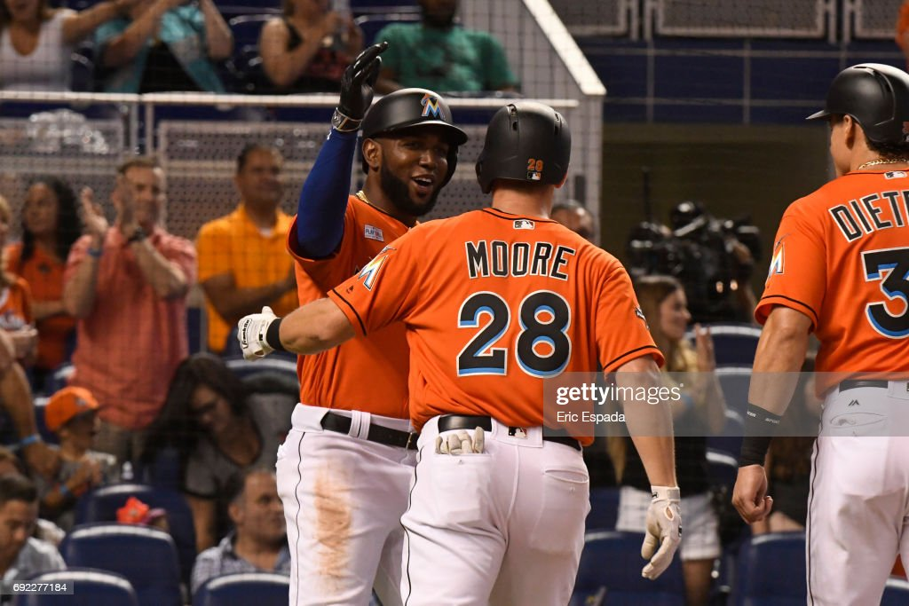 Marcell Ozuna #13 of the Miami Marlins congratulates Tyler Moore #28 after he hit a three-run home run in the second inning against the Arizona Diamondbacks at Marlins Park on June 4, 2017 in Miami, Florida.