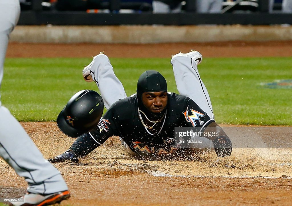 Marcell Ozuna #13 of the Miami Marlins dives home safely for a run in the second inning against the New York Mets at Citi Field on April 7, 2017 in the Flushing neighborhood of the Queens borough of New York City.