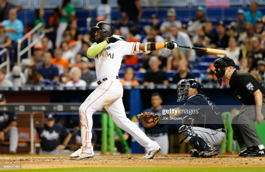 Marcell Ozuna #13 of the Miami Marlins hits a seventh-inning home run in front of Kurt Suzuki #24 of the Atlanta Braves at Marlins Park on October 1, 2017 in Miami, Florida.