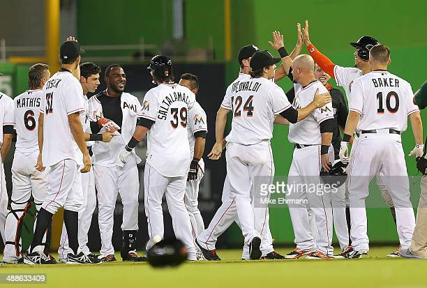 Marcell Ozuna of the Miami Marlins is congratulated after hitting a walk off sacrafice fly during a game against the New York Mets at Marlins Park on...