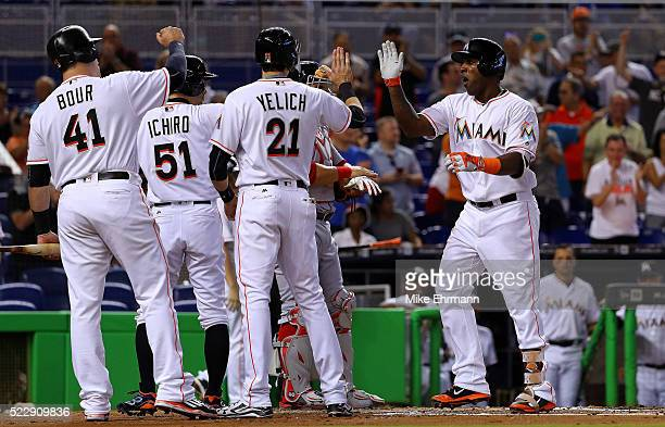 Marcell Ozuna of the Miami Marlins is congratulated after hitting a three run home run in the first inning during a game against the Washington...