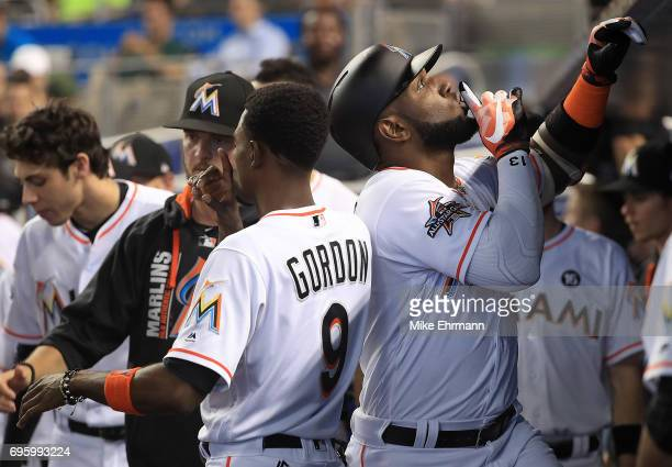 Marcell Ozuna of the Miami Marlins is congratulated by Dee Gordon after hitting a solo home run during a game against the Oakland Athletics at...