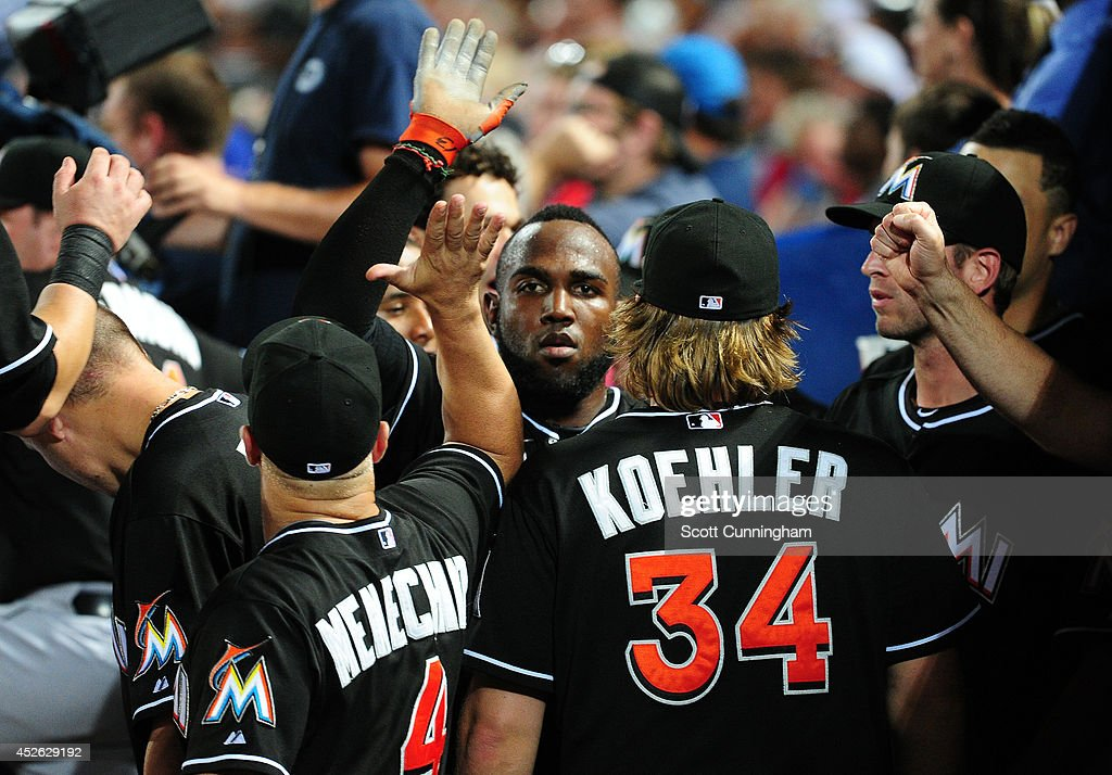 Marcell Ozuna #13 of the Miami Marlins is congratulated by teammates after scoring a ninth inning run against the Atlanta Braves at Turner Field on July 24, 2014 in Atlanta, Georgia.