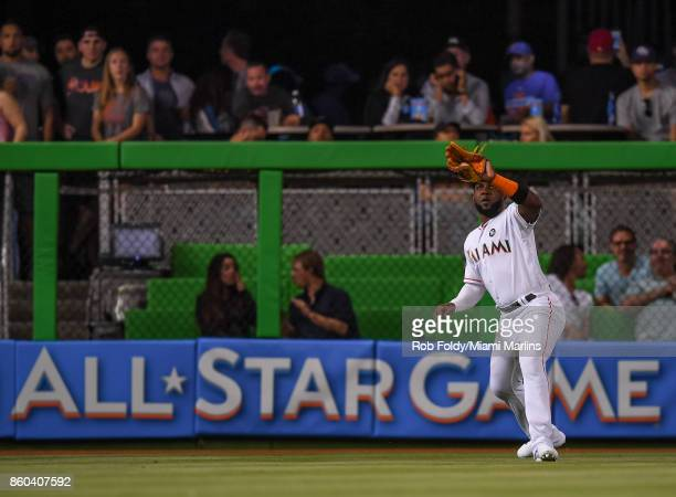 Marcell Ozuna of the Miami Marlins makes a catch in the outfield during the game against the New York Mets at Marlins Park on April 13 2017 in Miami...