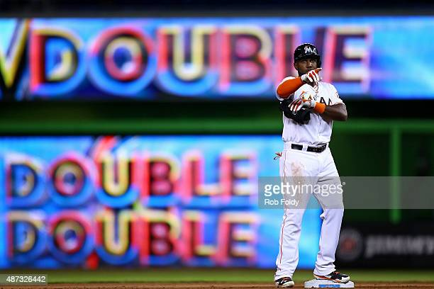 Marcell Ozuna of the Miami Marlins motions to the dugout after hitting a double during the seventh inning of the game against the Milwaukee Brewers...