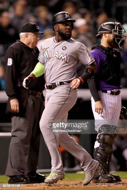 Marcell Ozuna of the Miami Marlins scores on a JT Realmuto RBI single in the fourth inning against the Colorado Rockies at Coors Field on September...