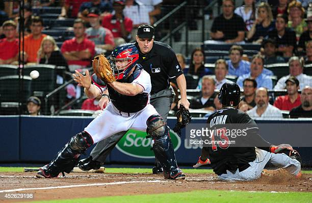 Marcell Ozuna of the Miami Marlins scores the go-ahead run in the ninth inning against Evan Gattis of the Atlanta Braves at Turner Field on July 24,...