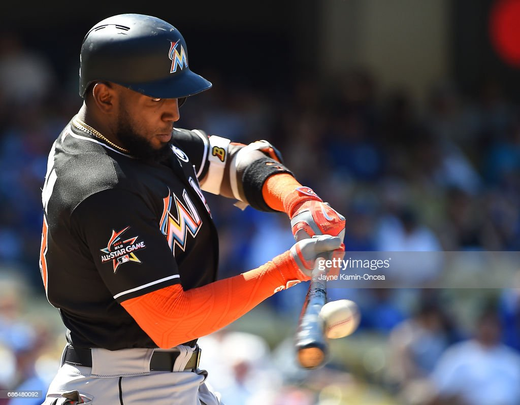 Marcell Ozuna #13 of the Miami Marlins singles in a run in the eighth inning against the Los Angeles Dodgers at Dodger Stadium on May 21, 2017 in Los Angeles, California.