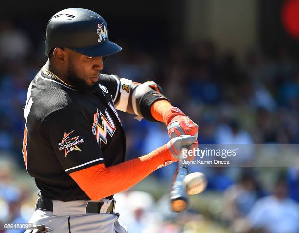 Marcell Ozuna of the Miami Marlins singles in a run in the eighth inning against the Los Angeles Dodgers at Dodger Stadium on May 21 2017 in Los...
