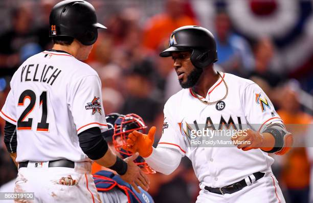 Marcell Ozuna of the Miami Marlins slaps hands with Christian Yelich after hitting a home run during the Opening Day game against the Atlanta Braves...