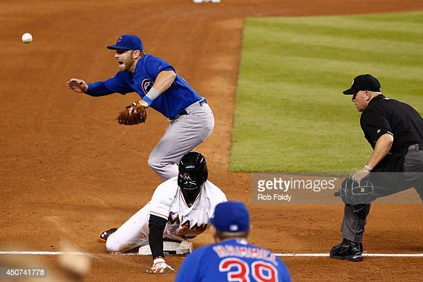 Marcell Ozuna of the Miami Marlins slides into third base ahead of the throw to Mike Olt of the Chicago Cubs during the sixth inning of the game at...