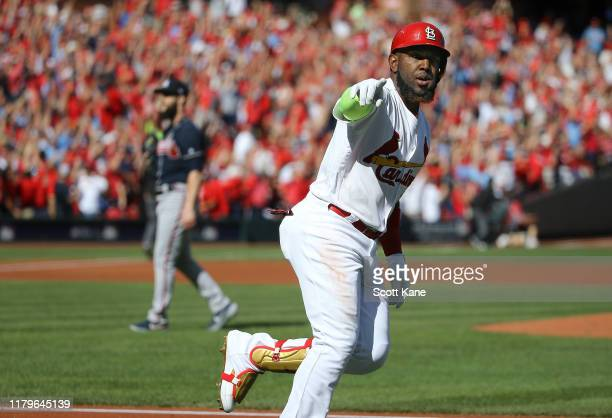 Marcell Ozuna of the St. Louis Cardinals celebrates as he rounds first base after his solo home run as Dallas Keuchel of the Atlanta Braves reacts...