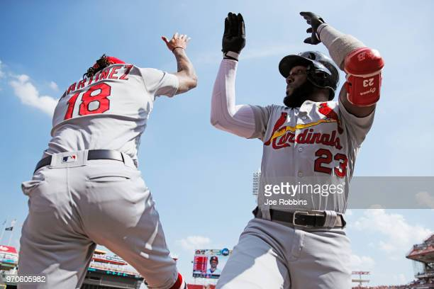 Marcell Ozuna of the St Louis Cardinals celebrates with Carlos Martinez after hitting a solo home run in the first inning against the Cincinnati Reds...