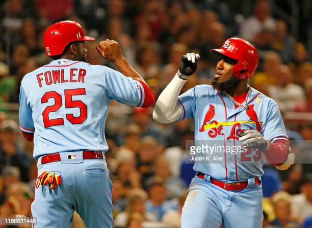 Marcell Ozuna of the St. Louis Cardinals celebrates with Dexter Fowler after hitting a three run home run in the third inning against the Pittsburgh...