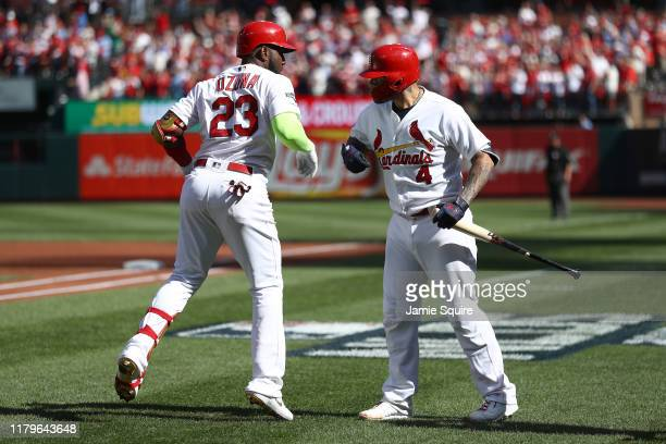 Marcell Ozuna of the St Louis Cardinals celebrates with teammate Yadier Molina after hitting a solo home run against the Atlanta Braves during the...
