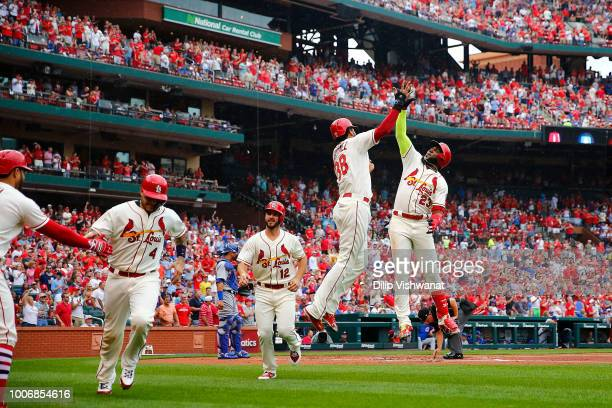 Marcell Ozuna of the St Louis Cardinals celebrates with teammates after hitting a grand slam against the Chicago Cubs in the first inning at Busch...