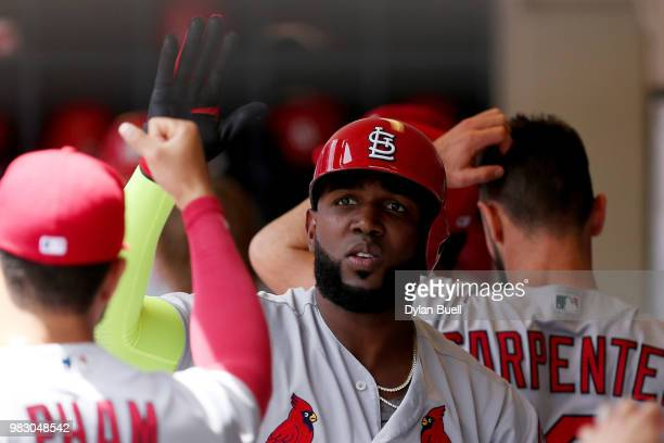 Marcell Ozuna of the St Louis Cardinals celebrates with teammates after hitting a sacrifice fly in the first inning against the Milwaukee Brewers at...