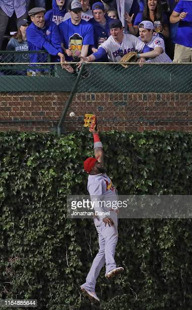 Marcell Ozuna of the St Louis Cardinals leaps in vain for a home run ball that lands in the left field basket hit by Carlos Gonzalez of the Chicago...