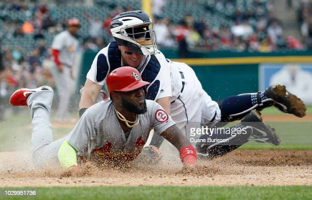 Marcell Ozuna of the St Louis Cardinals scores past the tag from catcher James McCann of the Detroit Tigers on a single by Kolten Wong of the St...