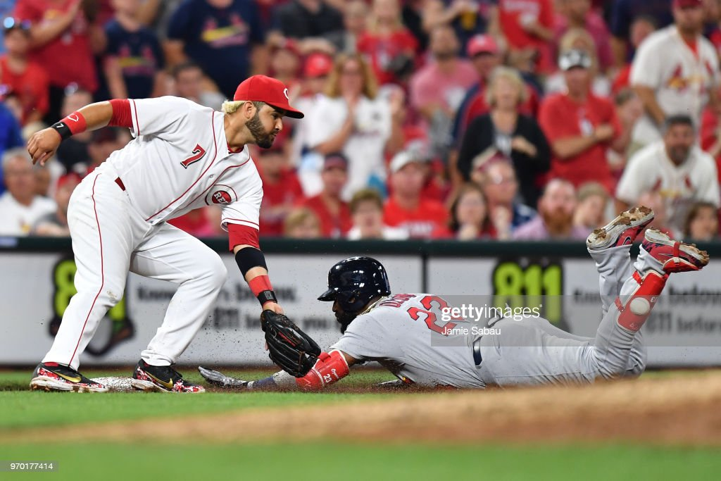 Marcell Ozuna #23 of the St. Louis Cardinals slides in safely for a triple in the eighth inning as Eugenio Suarez #7 of the Cincinnati Reds awaits the throw at Great American Ball Park on June 8, 2018 in Cincinnati, Ohio.