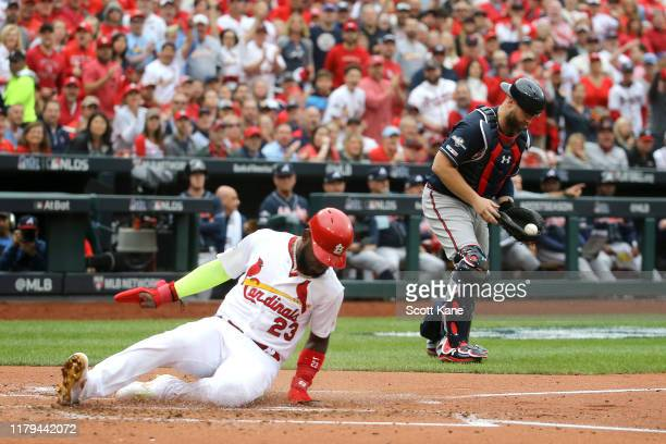 Marcell Ozuna of the St Louis Cardinals slides in safely past Brian McCann of the Atlanta Braves to score a run during the second inning in game...