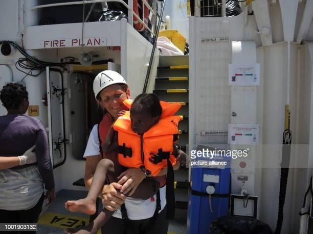 Marcella Kraay vonÄrzte ohne Grenzen hält am ein von einemSchlauchboot im Mittelmeer gerettetes Kind imArm Photo Lena Klimkeit/dpa