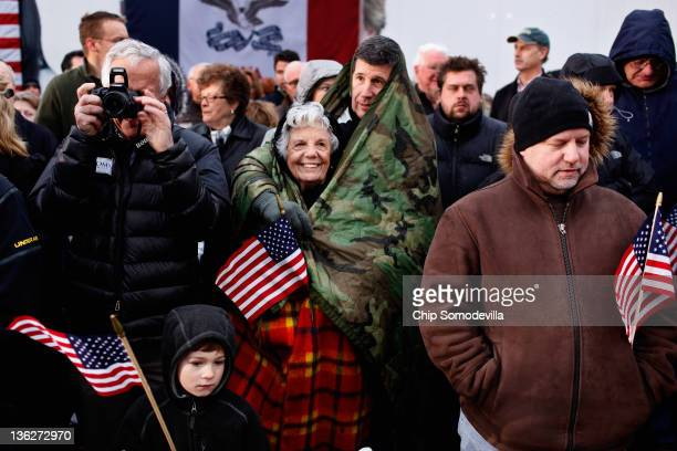 Marcella Yochum and her son Scott Yochum of West Des Moines take shelter under a camoflauge sleeping bag while waiting for the arrival of former...