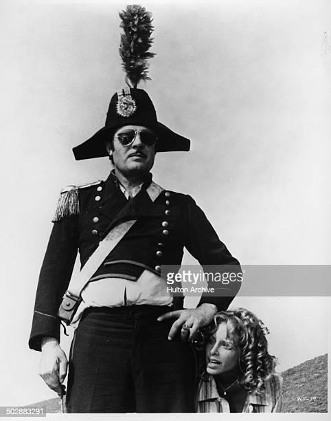 """Marcello Mastroianni stands in a costume with Sydne Rome in a scene of the movie """"What?"""" circa 1972."""