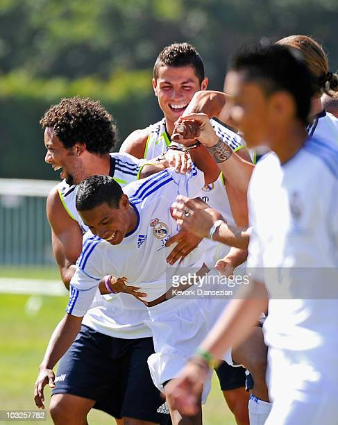 Marcelo and Cristiano Ronaldo of Real Madrid hug a local youth soccer player participating in the Adidas training after he scored a goal August 5...