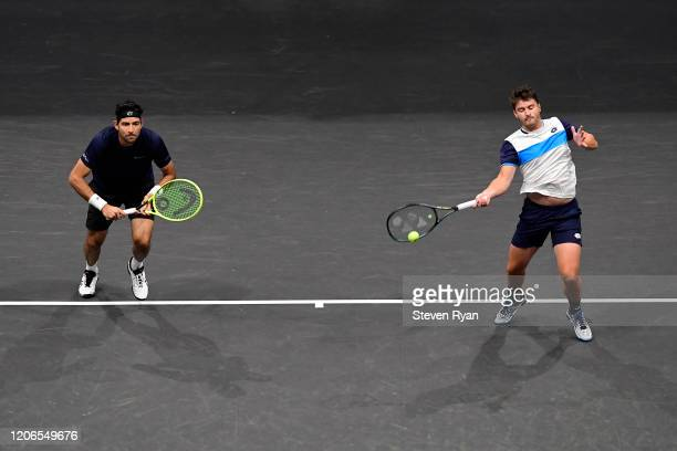 Marcelo Arevalo of El Salvador and Jonny O'Mara of Great Britain returns a shot during their Men's Double's semifinal match against Steve Johnson and...