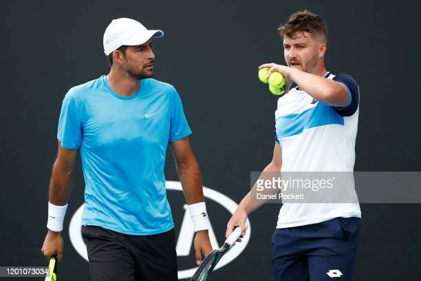 Marcelo Arevalo of El Salvador and Jonny O'Mara of Great Britain talk tactics during their Men's Doubles first round match against Hugo Dellien of...