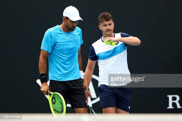 Marcelo Arevalo of El Salvador and Jonny O'Mara of Great Britain talk tactics in their Men's Doubles second round match against Jurgen Melzer of...