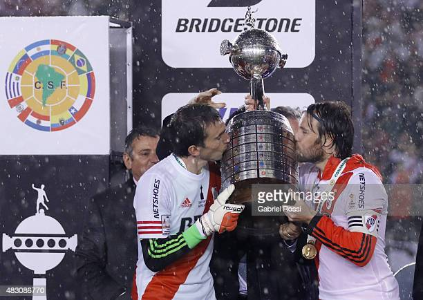 Marcelo Barovero and Fernando Cavenaghi of River Plate kiss the trophy after winning a second leg final match between River Plate and Tigres UANL as...