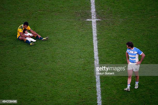 Marcelo Bosch of Argentina looks on as Will Genia of Australia sits on the field with his daughter Olivia during the 2015 Rugby World Cup Semi Final...
