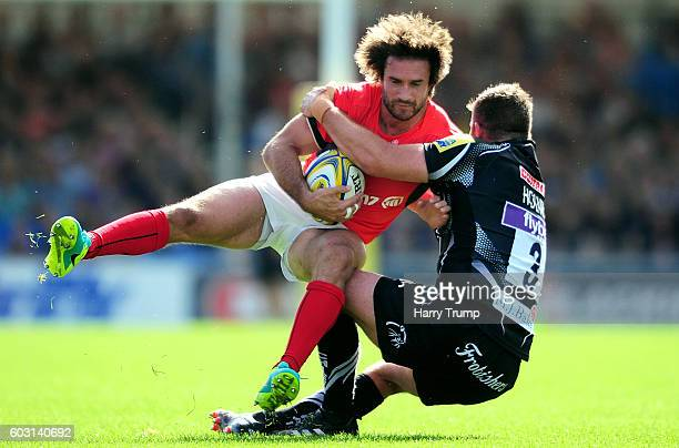 Marcelo Bosch of Saracens is tackled by Greg Holmes of Exeter Chiefs during the Aviva Premiership match between Exeter Chiefs and Saracens at Sandy...