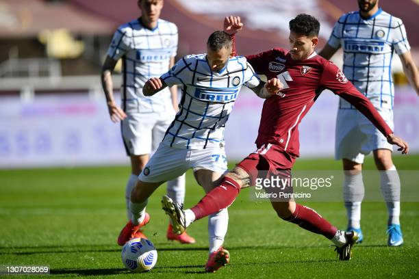 Marcelo Brozovic of Internazionale is challenged by Jean Freddi Greco of Torino FC during the Serie A match between Torino FC and FC Internazionale...