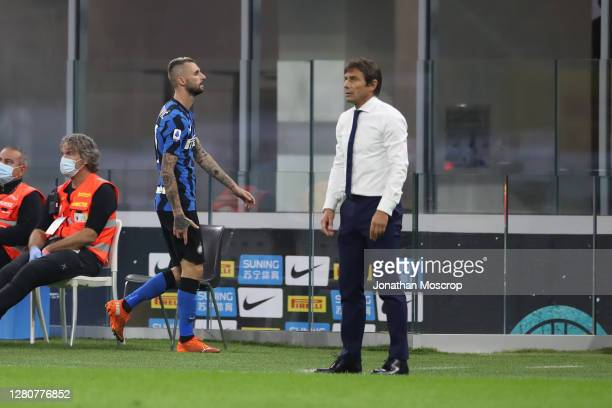 Marcelo Brozovic of Internazionale passes head coach Antonio Conte as he leaves the field of play with what appeared to be a hamstring injury during...