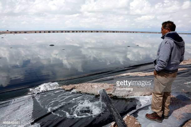 Marcelo Castro chief engineer and head of operations of the Bolivian state mining company's lithium plant looks out across a 65acre evaporation pool...