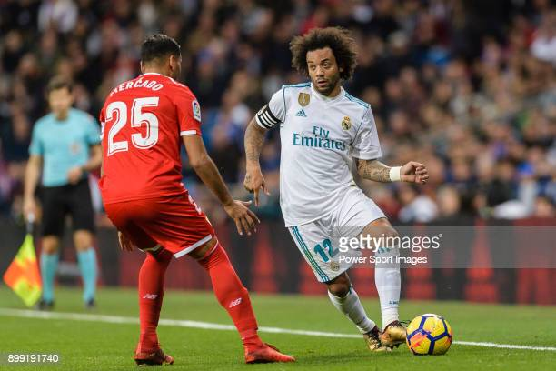 Marcelo da Silva of Real Madrid looks to bring the ball down while being defended by Gabriel Mercado of Sevilla FC during La Liga 201718 match...